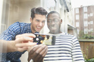 Two young male friends taking selfie behind patio glass - CUF33059
