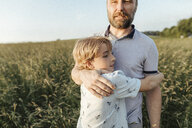 Father and son standing on a meadow hugging each other - KMKF00364