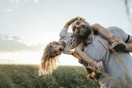 Mature man playing with his little daughter in nature - KMKF00376