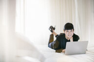 Portrait of mature businesswoman lying on bed using laptop in hotel room - CUF33109