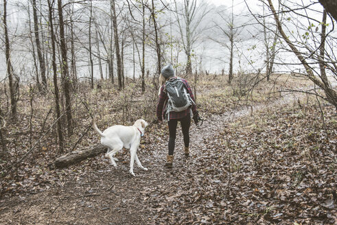 Young woman walking her dog in lakeside forest - ISF10560