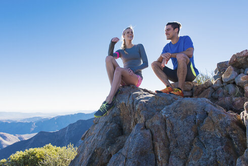 Trail running couple sitting chatting on rock formation, Pacific Crest Trail, Pine Valley, California, USA - ISF10590