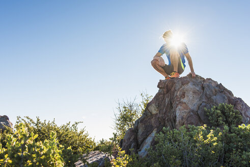 Male trail runner looking down from rock on Pacific Crest Trail, Pine Valley, California, USA - ISF10593