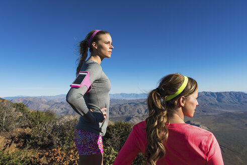 Two female trail running friends looking at view from Pacific Crest Trail, Pine Valley, California, USA - ISF10596