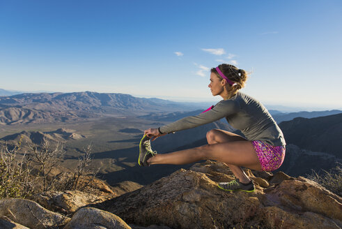 Rear view of young female trail runner crouching and touching toes,Pacific Crest Trail, Pine Valley, California, USA - ISF10599