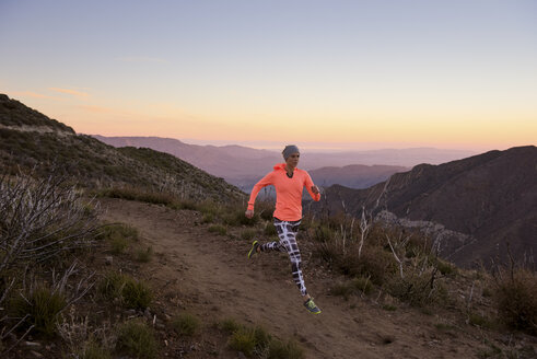 Rear view of young woman trail running down dirt track at dusk on Pacific Crest Trail, Pine Valley, California, USA - ISF10602