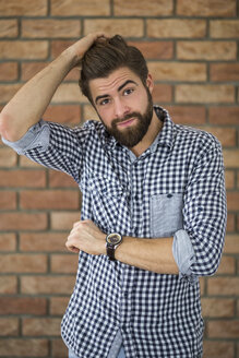 Portrait of bearded young man in front of brick wall scratching his head - AWF00059