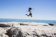 Young woman jumping over rocks, Scarborough Bluffs, Toronto, Ontario, Canada - ISF10689