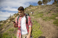 Young man at bottom of hill, using smartphone, friends trailing behind - ISF10704