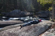 Male hiker lying on riverside rock, Rangeley, Maine, USA - ISF10758