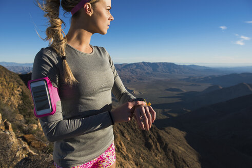 Young female trail runner checking stopwatch on Pacific Crest Trail, Pine Valley, California, USA - ISF10788