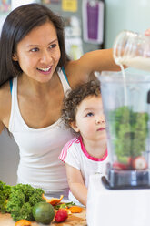 Mid adult woman making smoothie for toddler niece in kitchen - ISF10851