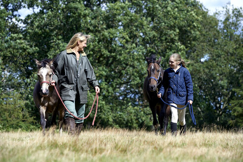 Mother and daughter walking horses in field - ISF10872