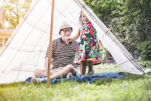 Portrait of girl and grandfather peeking from homemade garden tent - ISF10884