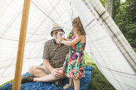 Mature man with granddaughter holding insect jar  in homemade garden tent - ISF10887