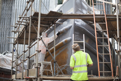Workers spray-painting boat hull in shipyard - ISF10983