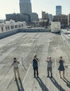 Businesspeople taking photographs with smartphones on roof terrace, Los Angeles, California, USA - ISF11013
