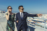 Businessman and businesswoman looking at view on roof terrace, Los Angeles, California, USA - ISF11016