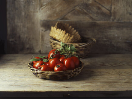 Fresh organic roma tomatoes in wicker basket - ISF11166