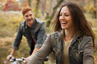 Young couple cycling along riverside in autumn - ISF11217