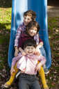 Siblings in a row between each others legs on playground slide smiling - ISF11226