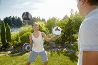 Man juggling balls in field - ISF11286