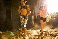 Joggers running under arch bridge, Arroyo Seco Park, Pasadena, California, USA - ISF11313