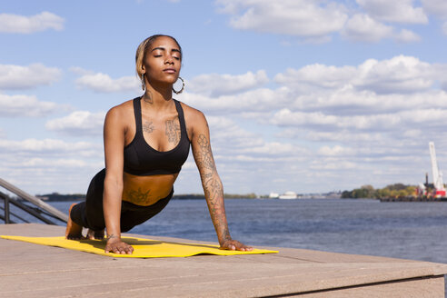 Young woman resting on hands by water in yoga position, eyes closed, Philadelphia, Pennsylvania, USA - ISF11355