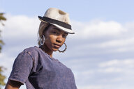 Low angle view of young woman wearing fedora and hoop earrings looking at camera - ISF11358