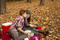 Romantic young couple having picnic in autumn forest - ISF11373