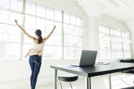 Businesswoman dancing by office window - ISF11385