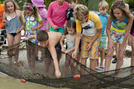 Front view of large group of kids collecting small fish from fishing net - ISF11481