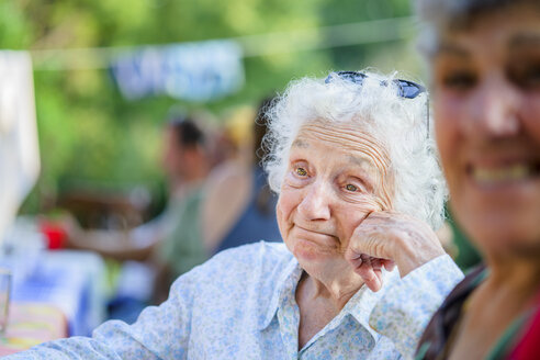 Senior woman daydreaming at tomato eating festival - ISF11520