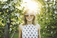 Young woman in orchard, flower in hair, wearing sunglasses looking at camera smiling - ISF11565