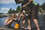 Father and daughters fishing, Kings Lake, Ontario, Canada - ISF11589