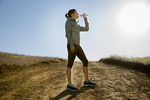 Silhouetted female runner drinking from water bottle on dirt track - ISF11595