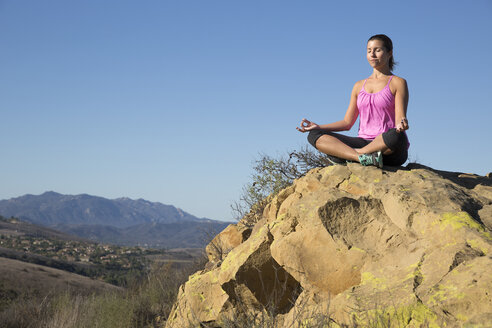 Mature woman practicing yoga lotus pose on hill, Thousand Oaks, California, USA - ISF11598