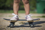 Legs of girl wearing canvas shoes standing on skateboard - ISF11604