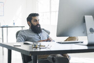 Bearded businessman sitting in front of computer - ISF11607