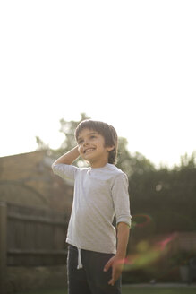 Low angle view of boy in garden hand on head looking away smiling - ISF11685