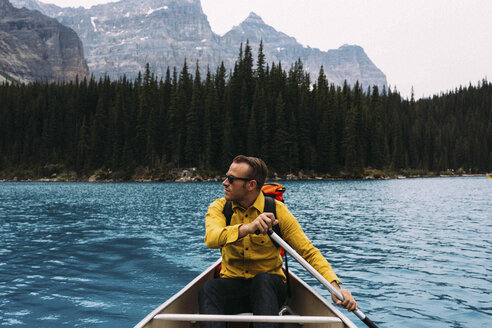 Front view of mid adult man paddling canoe, looking away, Moraine lake, Banff National Park, Alberta Canada - ISF11688