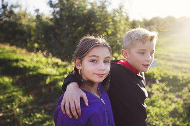 Boy in orchard with arms around girl, looking at camera smiling - ISF11712