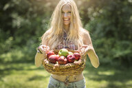 Portrait of young woman holding up basket of fresh apples in garden - ISF11826
