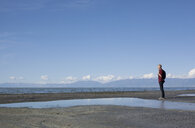 Side view of young man standing at waters edge looking out, Great Salt lake, Utah, USA - ISF11868