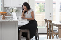 Young woman, sitting at kitchen counter with coffee and laptop - ISF11913