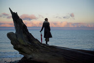 Woman leaning on umbrella standing on large driftwood tree trunk on beach - ISF11937