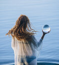 Rear view of young woman with long red hair standing in lake holding crystal ball - ISF11943