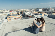 Businesswomen taking selfie with smartphone on roof terrace, Los Angeles, California, USA - ISF12021