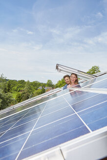 Young couple looking out of roof window with solar panels - ISF12057