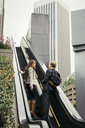 Businesswoman and man moving up escalator, Los Angeles, USA - ISF12063